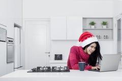 Härlig kvinna med jultomten hatt och bärbar dator Royaltyfria Bilder