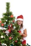 Härlig kvinna med jultomtenhatten som kikar bak julgranen royaltyfri fotografi