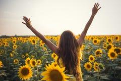 Härlig kvinna med långa hårhänder upp i ett fält av solrosor royaltyfri foto