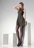 Härlig kvinna med långa sexiga ben i läderklänningen som poserar i studion - full kropp Arkivbilder