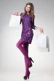 Härlig kvinna med långa sexiga ben som rymmer shoppingpåsar Royaltyfri Foto