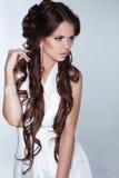 Härlig kvinna med långt brunt hår som bär i vit klänningisolator Arkivbild