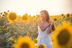 Härlig kvinna med långt hår i ett fält av solrosor i set Arkivbild