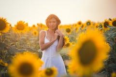 Härlig kvinna med långt hår i ett fält av solrosor i set Royaltyfri Bild