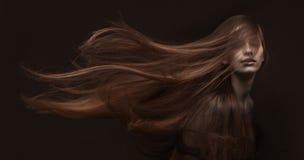 Härlig kvinna med långt hår på mörk bakgrund Fotografering för Bildbyråer