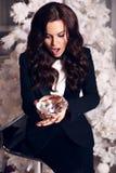 Härlig kvinna med långt mörkt hår som bär den eleganta dräkten som rymmer en stor dekorativ diamant Royaltyfri Fotografi