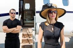 Härlig kvinna med livvakten Against Private Jet Royaltyfri Bild
