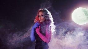 Härlig kvinna med ljust hår En mystisk stående på bakgrunden av dimma och en stjärnklar himmel royaltyfri bild