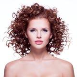 Härlig kvinna med lockigt hår för brunett Arkivbild