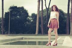 Härlig kvinna med lockigt hår som ler och poserar Stads- look Arkivfoto
