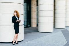 Härlig kvinna med lockigt hår, spensliga ben, den bärande svarta dräkten och hög-heeled skor, hållande anteckningsbok i händer so royaltyfria bilder