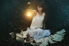 Härlig kvinna med lyktan i en mörk skog arkivbild