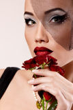 Härlig kvinna med mörker - röda rosor blommar skyler in retro glamour Arkivfoto