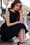 Härlig kvinna med mörkt hår i elegant klänning som går på set fotografering för bildbyråer