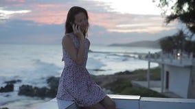 Härlig kvinna med mobiltelefonen på en stenig strand på solnedgången stock video