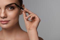 Härlig kvinna med ny makeup och borste för ögonbryn Royaltyfria Foton
