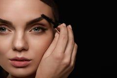 Härlig kvinna med ny makeup och borste för ögonbryn Arkivfoton