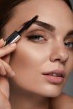 Härlig kvinna med ny makeup och borste för ögonbryn Royaltyfri Fotografi