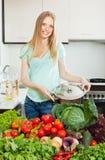 Härlig kvinna med nya grönsaker och gräsplaner Fotografering för Bildbyråer