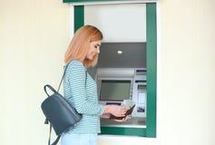 Härlig kvinna med pengar nära bankomaten royaltyfri foto