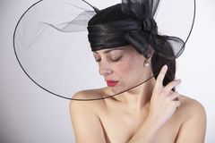 Härlig kvinna med röda kanter och stängda ögon med ledsen blick och den svarta hatten retro mode royaltyfri bild