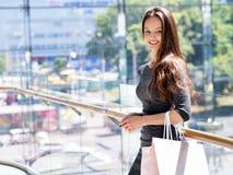 Härlig kvinna med shoppingpåsar i stor galleria arkivbild