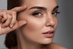 Härlig kvinna med skönhetframsidan, yrkesmässig makeup applicera genomskinlig fernissa för omsorgshud Arkivfoton