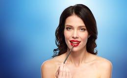 Härlig kvinna med sminkborsten för läppstift Royaltyfri Foto