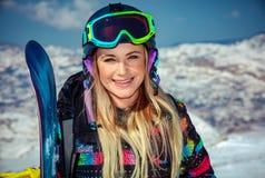 Härlig kvinna med snowboarden arkivfoto