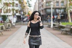 Härlig kvinna med solglasögon som talar vid telefonen Arkivbilder