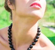 Härlig kvinna med svarta pärlor som göras av den nya svarta vinbäret Arkivfoto