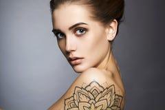 Härlig kvinna med tatueringen och smink Arkivfoto