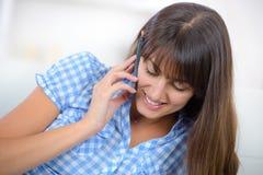Härlig kvinna med telefonen hemma arkivfoton