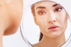 Härlig kvinna med vitiligoen som ser i spegeln Arkivbilder