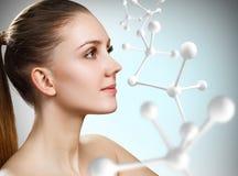 Härlig kvinna nära den stora vita molekylstrukturen royaltyfria bilder