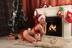 Härlig kvinna nära spisen i vinterhus selebrating jul Arkivbilder