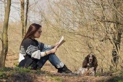 Härlig kvinna och bruntcockerspaniel i skogen Arkivfoton