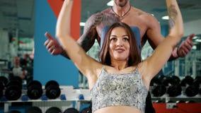 Härlig kvinna och en brutal man på idrottshalllyftande hanteln Lyftande hantel för ursnygg kvinna med hennes make på idrottshalle lager videofilmer