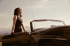 Härlig kvinna och gammal bil, sixtiesstil Royaltyfri Bild
