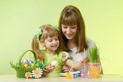 Härlig kvinna och hennes dotter som färgar påskägg på tabellen royaltyfri fotografi