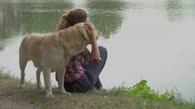 Härlig kvinna och labrador nära floden stock video