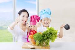 Härlig kvinna och ungar som är klara att laga mat Royaltyfria Bilder