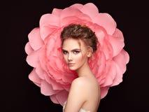 Härlig kvinna på bakgrunden av en stor blomma fotografering för bildbyråer