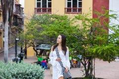 Härlig kvinna på den vita klänningen som bara går på omge för väggar av den koloniala staden av Cartagena de Indias arkivbilder