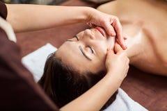 Härlig kvinna på en ansikts- massage på en brunnsortsalong royaltyfria foton