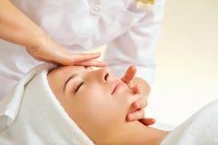 Härlig kvinna på en ansikts- massage på en brunnsortsalong royaltyfri foto