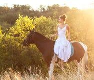 Härlig kvinna på en häst Arkivbilder