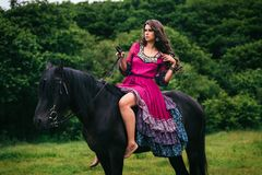 Härlig kvinna på en häst Arkivbild