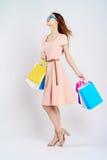 Härlig kvinna på en ljus bakgrund med exponeringsglas, shopping, shopping Royaltyfria Bilder