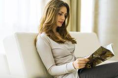 Härlig kvinna på en soffa som läser ett papper i vardagsrummet royaltyfri fotografi